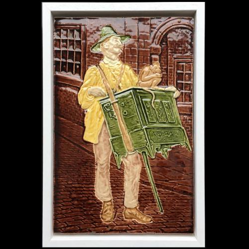 c.1900 relief moulded porcelain plaque with street organ grinder, framed