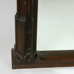 A victorian gothic oak mirror the design closely based on the South Door of the Parish church of the St Mary the Virgin Nottingham