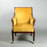 A Regency mahogany library armchair having reeded downswept scroll arms re-upholstered in a mustard yellow draylon raised on sabre legs